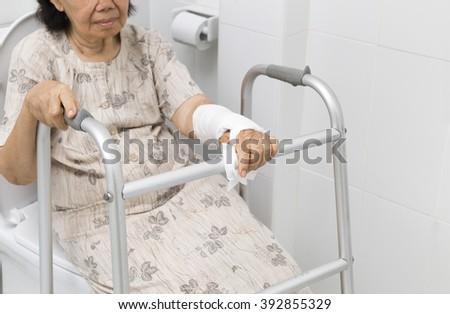 Senior women using the toilet with walker. - stock photo