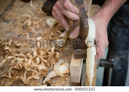 Senior woodworker or carpenter doing woodworking on a plank of wood in workshop with manual plane  - stock photo