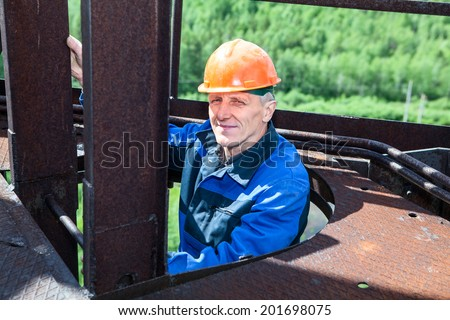 Senior worker climbing up for maintenance works - stock photo