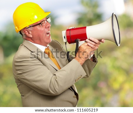 Senior Worker Shouting With Megaphone, Outdoor - stock photo
