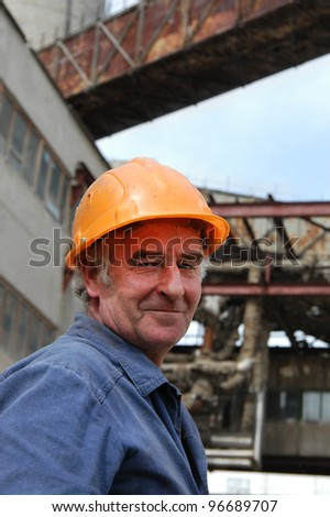 Senior worker with hard yellow hat smiling. Elderly worker - stock photo