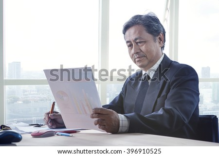 senior working man reading business paper report on working table use for people in office life