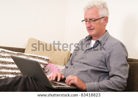 Senior working on a laptop while sitting on the couch