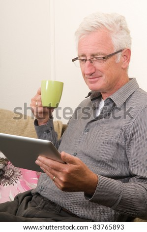 Senior working on a tablet pc while sitting on the couch - stock photo