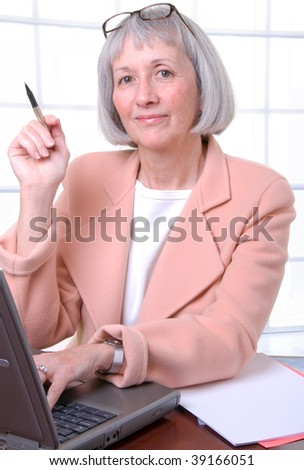 Senior working woman busy at her desk - stock photo