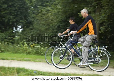 Seniors biking on a sandy path with motion in the picture. Focus is on the woman. - stock photo