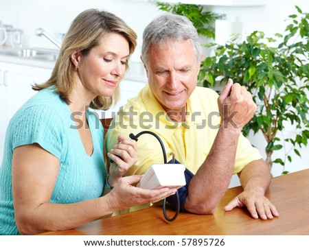 Seniors couple at home measuring blood pressure. Home monitoring - stock photo