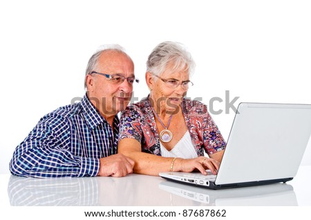 Seniors couple working with laptop at home - stock photo