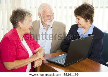 Seniors discuss their retirement with a financial advisor. - stock photo