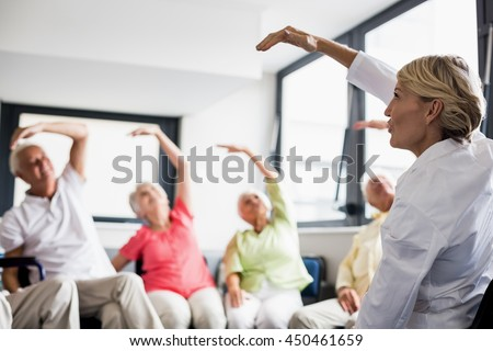 Seniors doing exercised in a retirement home - stock photo