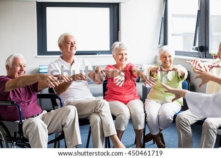 Seniors doing exercises in a retirement home - stock photo