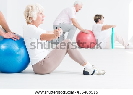 Seniors exercising in light and spacious interior with stretching tapes and gym balls