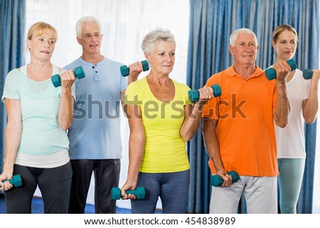 Seniors exercising with weights during sports class