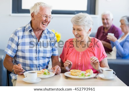 Seniors having lunch together in a retirement home - stock photo