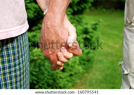 seniors holding hands in with natural background - stock photo