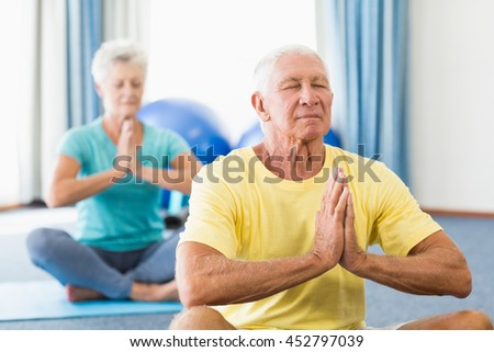 Seniors performing yoga in a studio