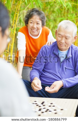seniors play weiqi with friends in the park - stock photo