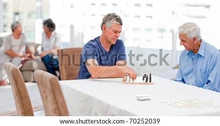 Seniors playing chess at home - stock photo
