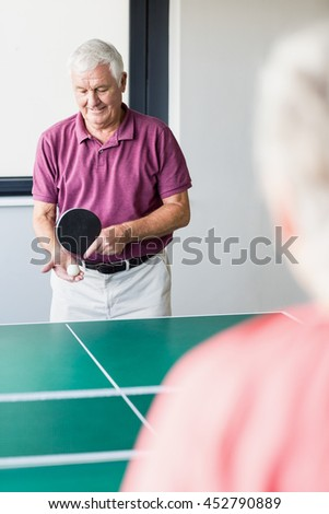 Seniors playing ping-pong in a retirement home - stock photo