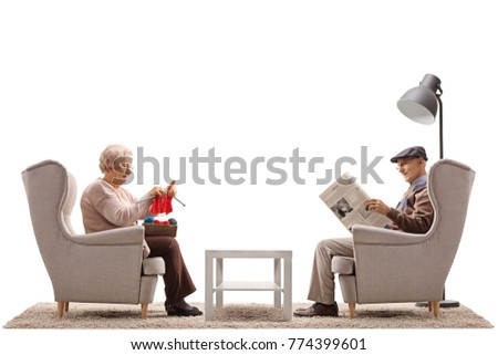 Seniors sitting in armchairs with one of them knitting and the other reading a newspaper isolated on white background