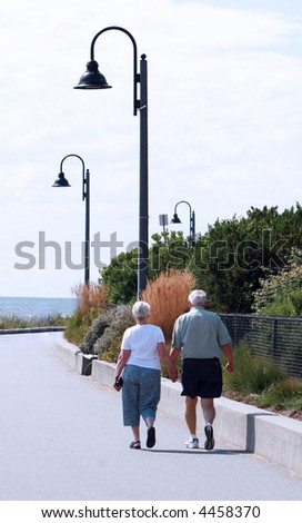 Seniors walking and holding hands as they stroll in the sun - stock photo