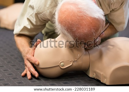 Seniror first aid student practitcing CPR on a dummy.  - stock photo