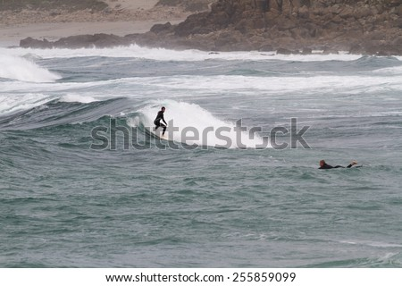 SENNEN COVE, CORNWALL, ENGLAND - 22 OCTOBER 2014: Surfers catching a wave on a cold autumn day,  on 22 October 2014 in Sennen Cove cornwall England. - stock photo
