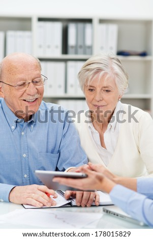 Senor couple in a business presentation leaning forwards to look at information on a tablet computer held out by their business broker - stock photo