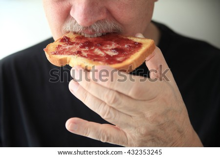 Senor man eating buttered toast spread with grape jam