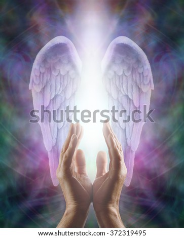 Sensing Angelic Energy - Male hands reaching up into a pair of lilac Angel wings with white light flowing down, on an intricate multicolored energy formation background                               - stock photo