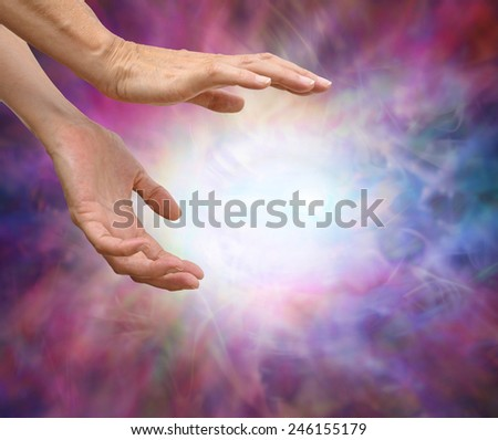 Sensing Reiki Energy - Pair of female hands reaching into energy formation surrounded by an intricate multicolored energy field - stock photo