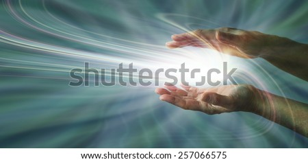 Sensing Supernatural Energy - Parallel female hands with a swirling light burst between on a blue energy field background - stock photo