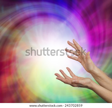 Sensing Vortex Energy Field - Pair of female hands reaching upwards into a vibrant energy vortex field with plenty of copy space           - stock photo