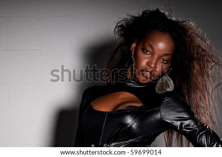 Sensual African American with leather catsuit posing. - stock photo