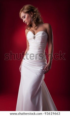 Sensual attractive blond hair bride posing over red background. Studio shot, series of photos - stock photo