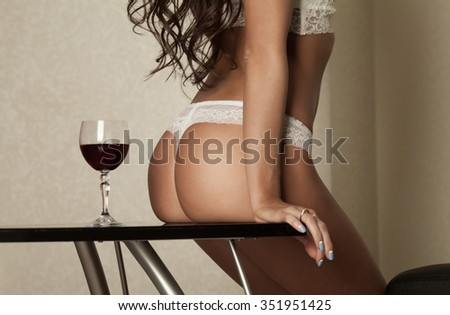 Sensual attractive brunette woman posing over the window wearing sexy lingerie. Slim girl. Great buttocks in a bikini. Fashion shot. Sexy girl in hotel room. - stock photo
