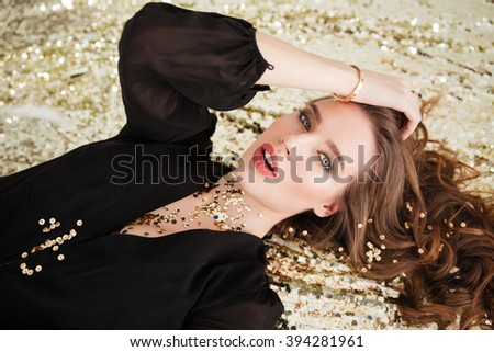 Sensual attractive young woman with sequins on her face lying over glittering background - stock photo