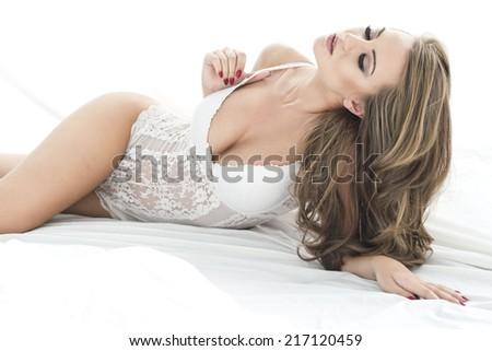 Sensual beautiful blonde woman posing in elegant lingerie in bed.   - stock photo