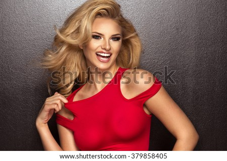 Sensual beautiful blonde woman posing in red dress. Girl with long curly hair.  - stock photo