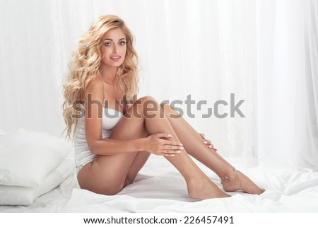 Sensual beautiful blonde woman sitting on bed, relaxing, looking at camera.