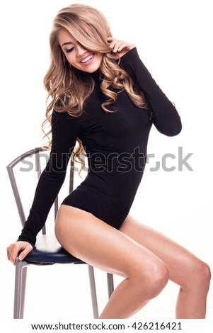 Sensual beautiful blonde woman sitting on the chair. Sexy pose. White background. - stock photo