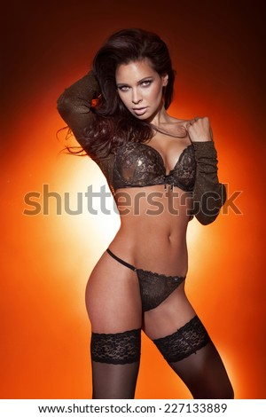 Sensual beautiful brunette woman posing in sexy lingerie, looking at camera.