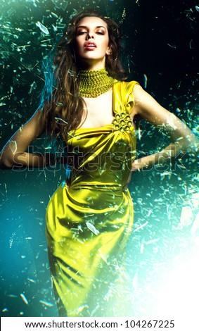 sensual beautiful woman in green dress and broken glass - stock photo
