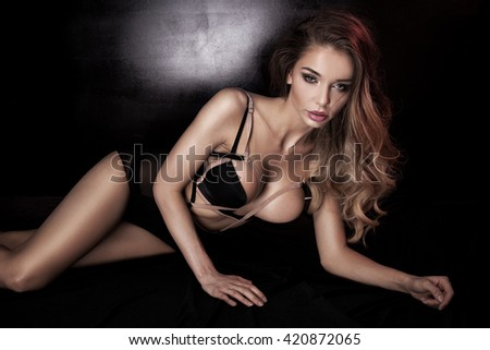 Sensual beautiful woman wearing black lingerie, lying in bed. Sexy body. Glamour makeup.