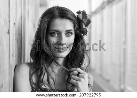 sensual beautiful young lady with shadow from window blinds having fun looking at camera happy smiling on sun lighted window blinds copy space background, black and white closeup portrait  - stock photo