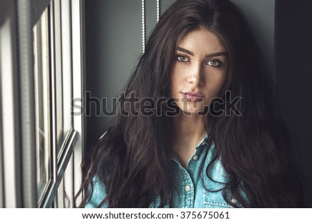 Sensual Beautiful Young Woman Sitting Near The Window. Attractive Model Girl. Curly Brunette Hair. - stock photo