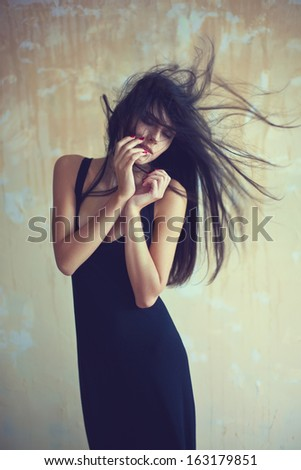 Sensual beautiful young woman with developing hair on textured background - stock photo