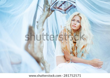 sensual beauty portrait of young blonde woman with birdcage. Soft focus. - stock photo