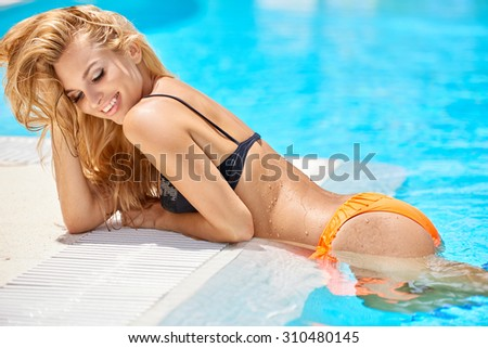 Sensual blond girl in enjoys her vacation time in swimming pool, she wearing black and orange bikini - stock photo