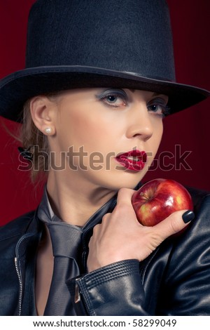 Sensual blond girl wearing a hat, offering an apple - stock photo